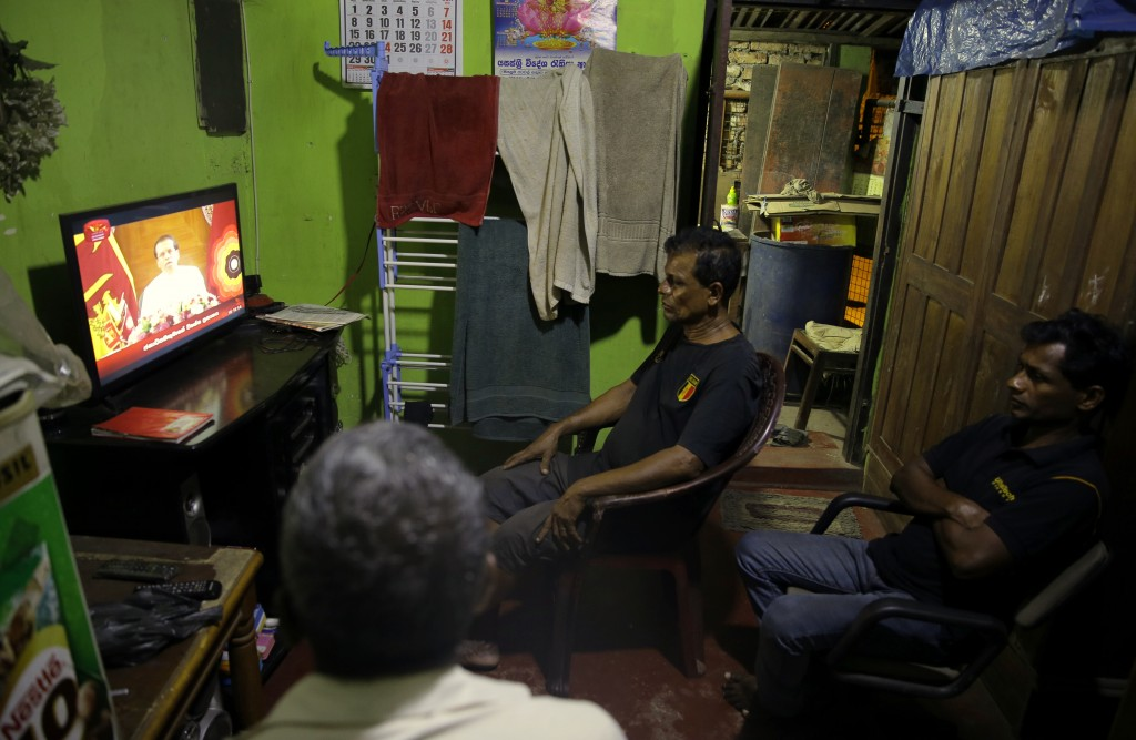FILE - In this Oct. 28, 2018 file photo, Sri Lankans watch a televised speech by president Maithripala Sirisena at their residence in Colombo, Sri Lan...