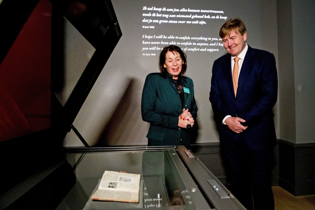 Dutch King Willem-Alexander, right, looks at Anne Frank's diary, foreground, displayed in the new Diary Room at the renovated Anne Frank House Museum