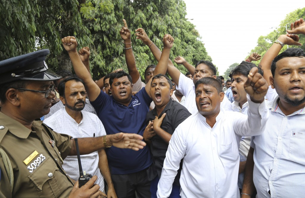 FILE - In this Nov. 14, 2018 file photo, supporters of newly appointed Prime Minister Mahinda Rajapaksa protest outside parliament gate following the