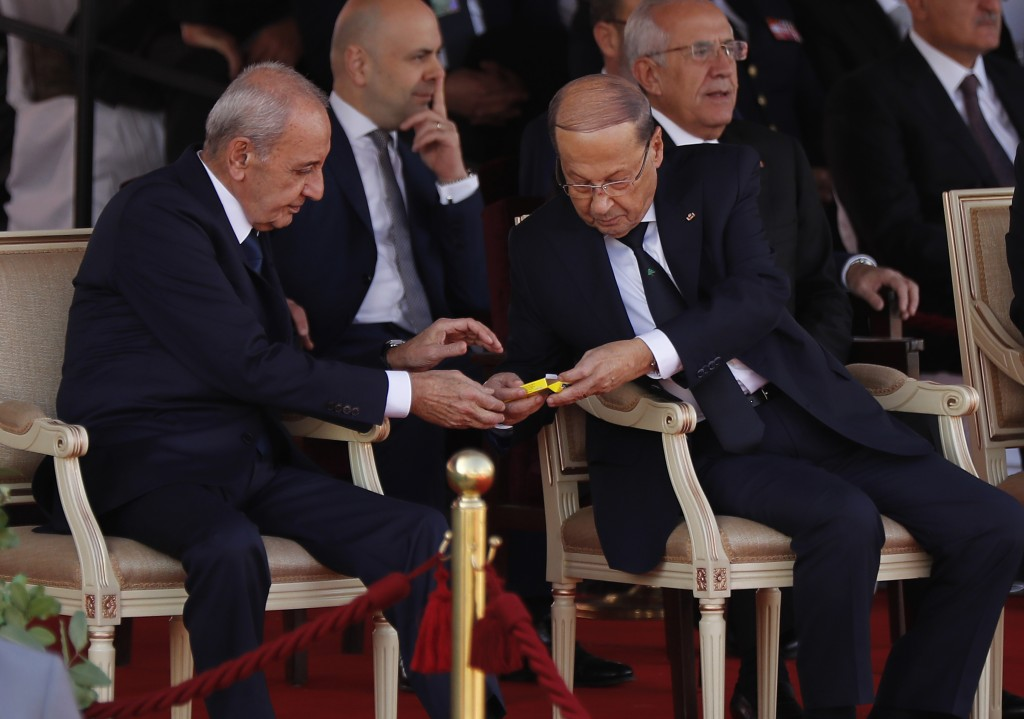 Lebanese President Michel Aoun, center right, gives candy to Lebanese Parliament Speaker Nabih Berri, during a military parade to mark the 75th annive
