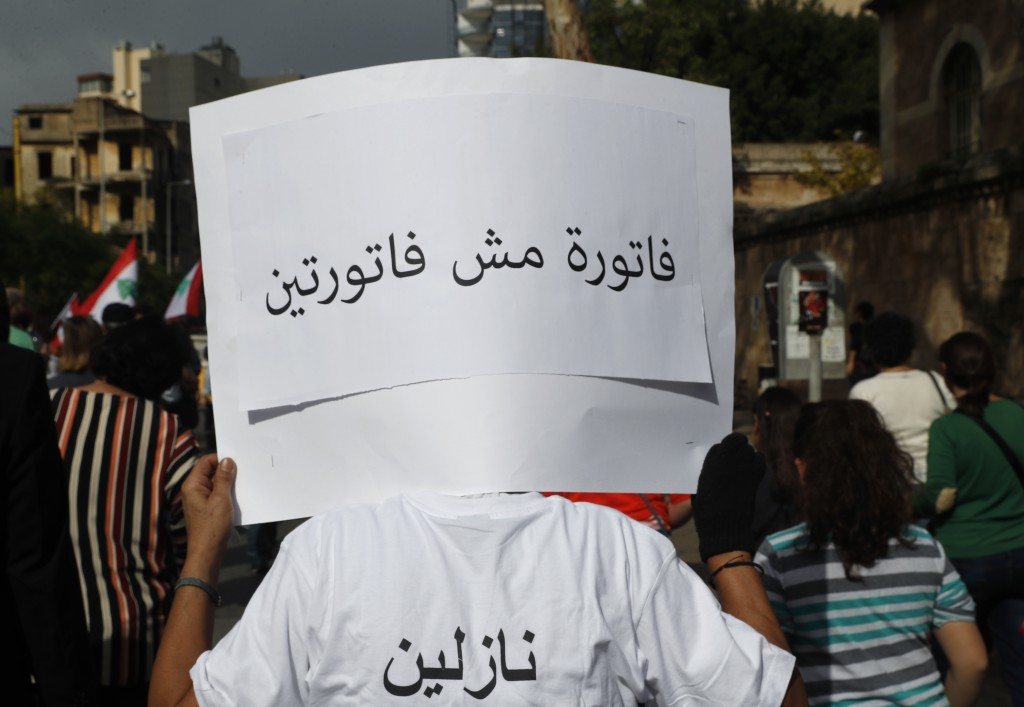"A Lebanese protester holds an Arabic placard that reads: ""One bill not two bills,"" during a protest against corruption and the failure of long-serving..."