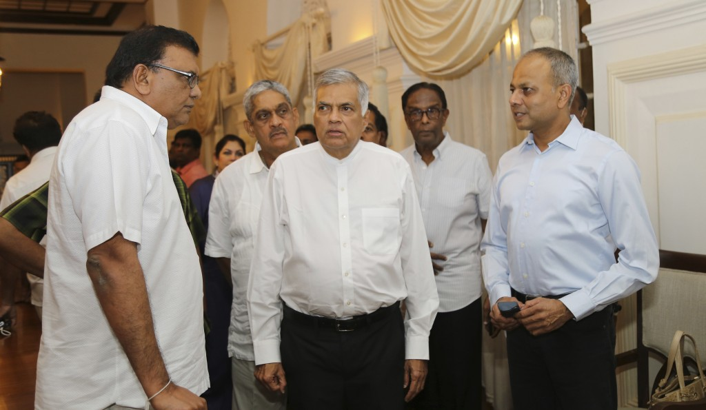 FILE - In this Oct. 26, 2018 file photo, Sri Lanka's sacked Prime Minister Ranil Wickremesinghe, center, speaks with party members at his official res...