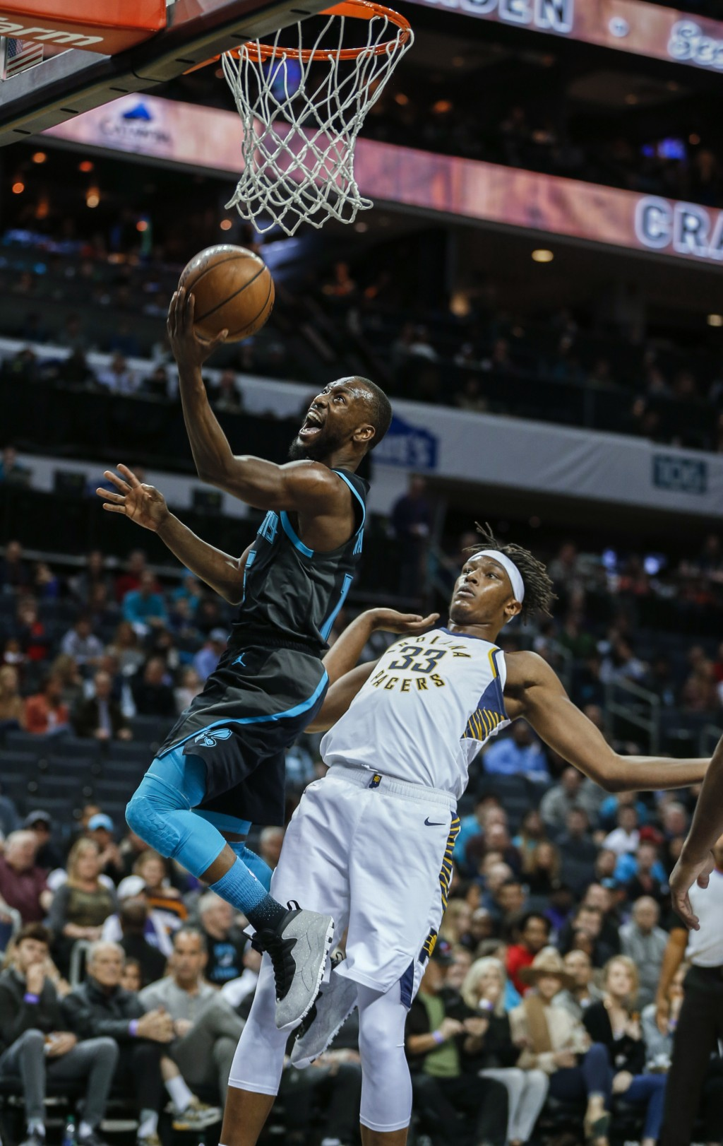 Charlotte Hornets guard Kemba Walker, left, drives to the basket in front of Indiana Pacers center Myles Turner during the first half of an NBA basket