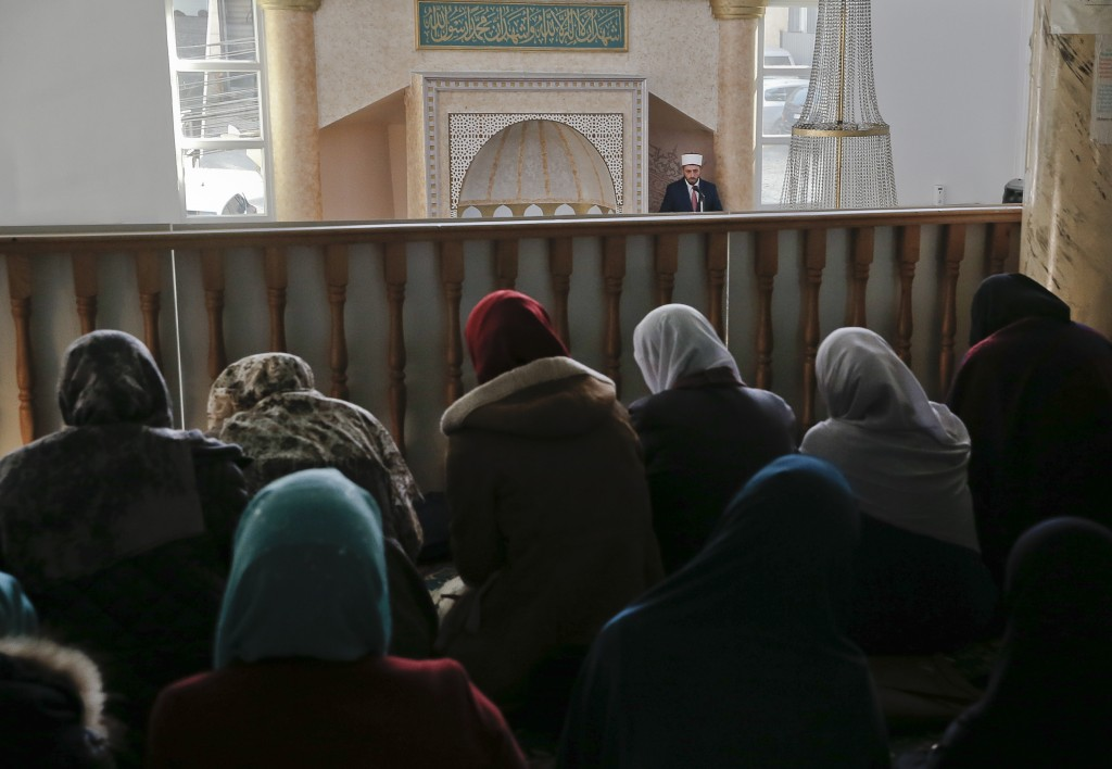 An Imam leads the congregation during the Friday prayer as muslim women attend in a secluded balcony inside Hasan Beg mosque at Kater Llullat neighbor