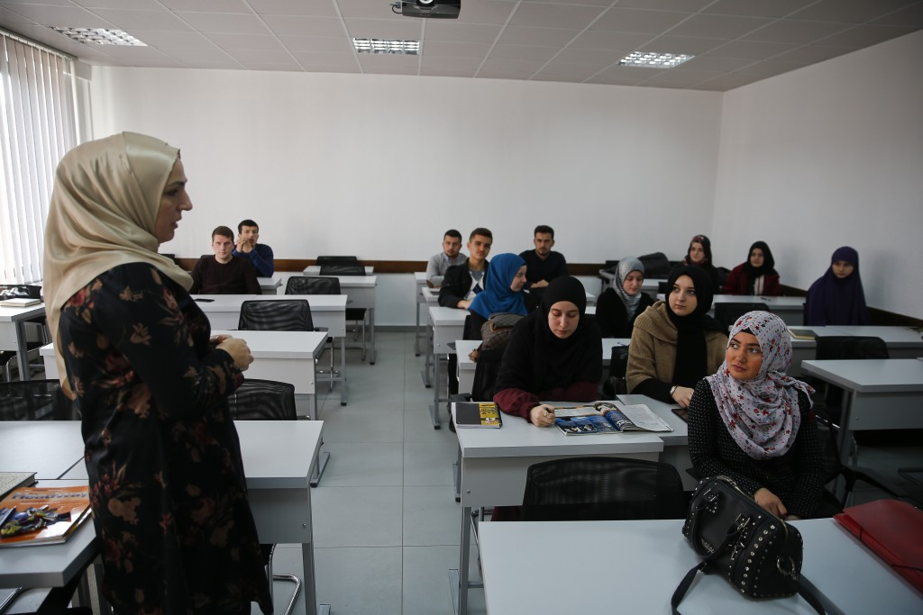 Best Ismaili, left, an english teacher talks to her students at the Faculty of Islamic Studies in Kosovo presents her work during an english class in