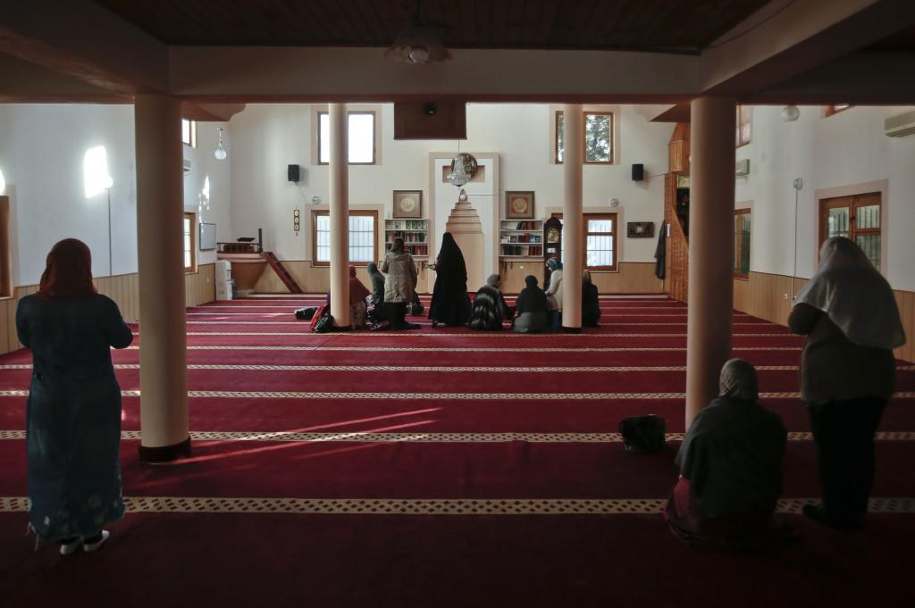 Muslim women pray before they attend a class insid...