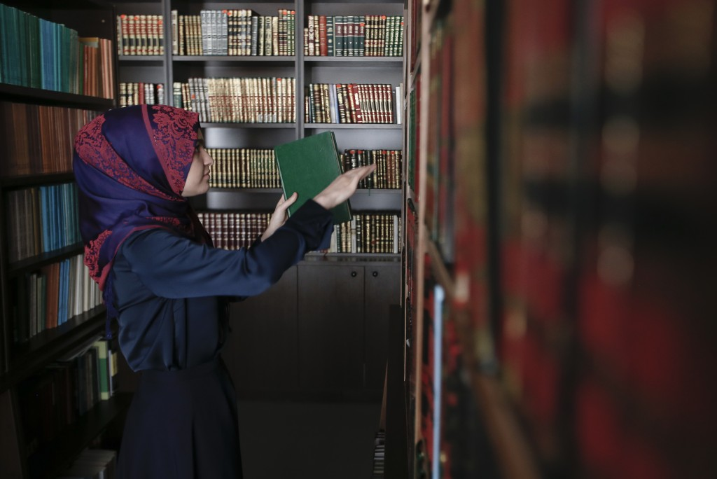 Enisa Bekteshi, student takes a book inside the library of the Faculty of Islamic Studies in Kosovo capital Pristina on Friday, Nov. 9, 2018. In Kosov