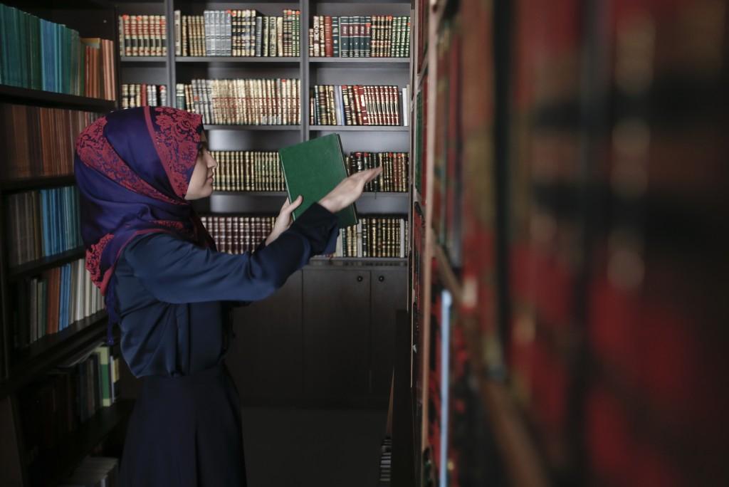 Enisa Bekteshi, student takes a book inside the li...