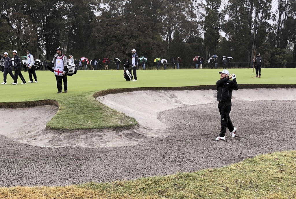 Tyrrell Hatton of England, bottom right, plays out a fairway bunker on the first hole during the second round of the World Cup of Golf tournament at t