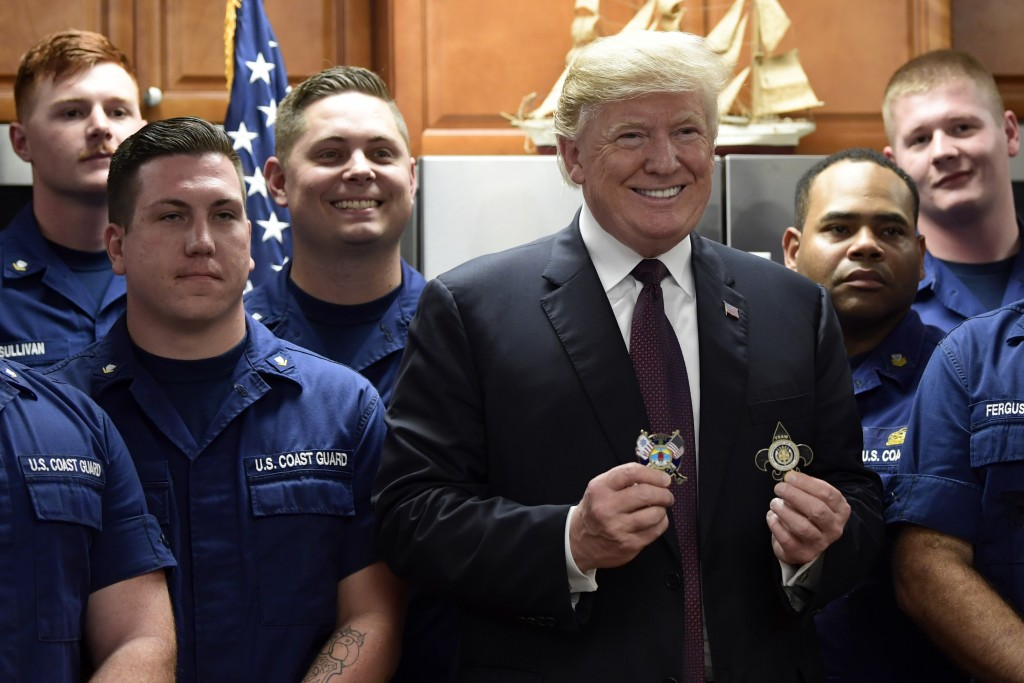 President Donald Trump meets and poses for a photo with members of the U.S. Coast Guard stationed at United States Coast Guard Station Lake Worth Inle