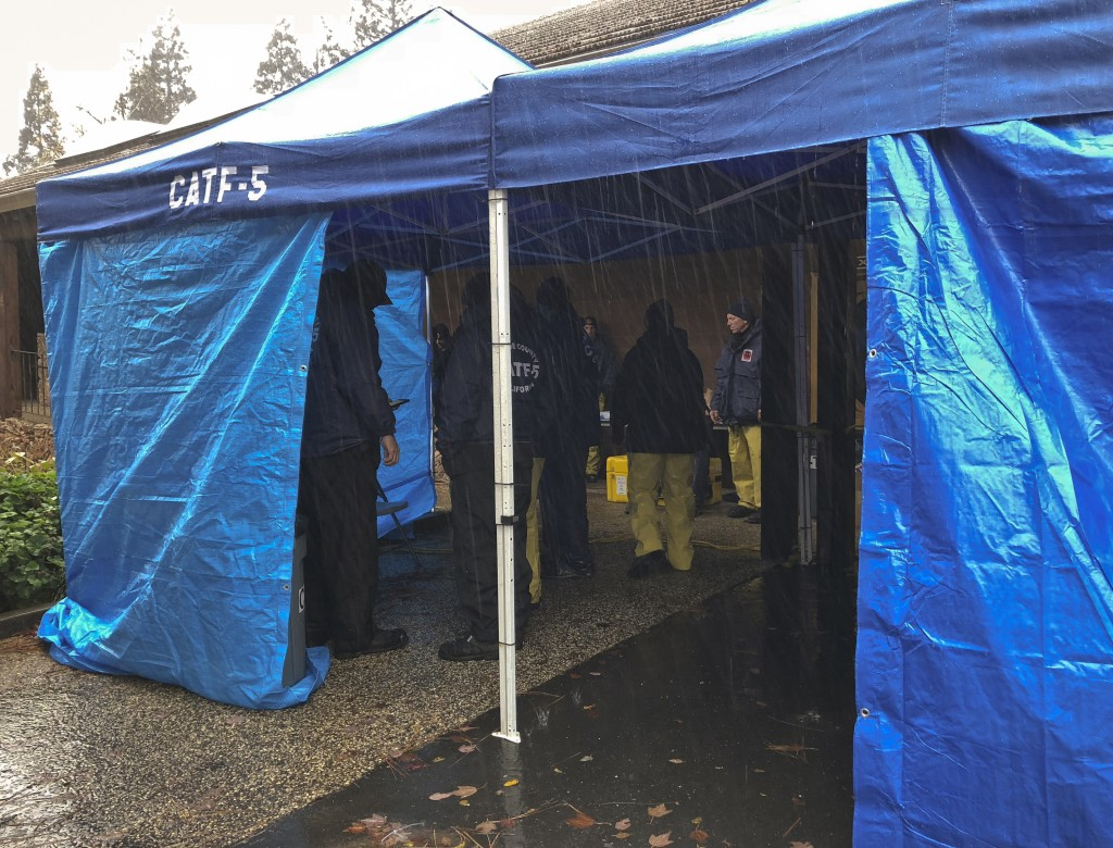 National Urban Search & Rescue Response System Orange County CATF-5 team members take cover from the rain in Paradise, Calif., Friday, Nov. 23, 2018. ...