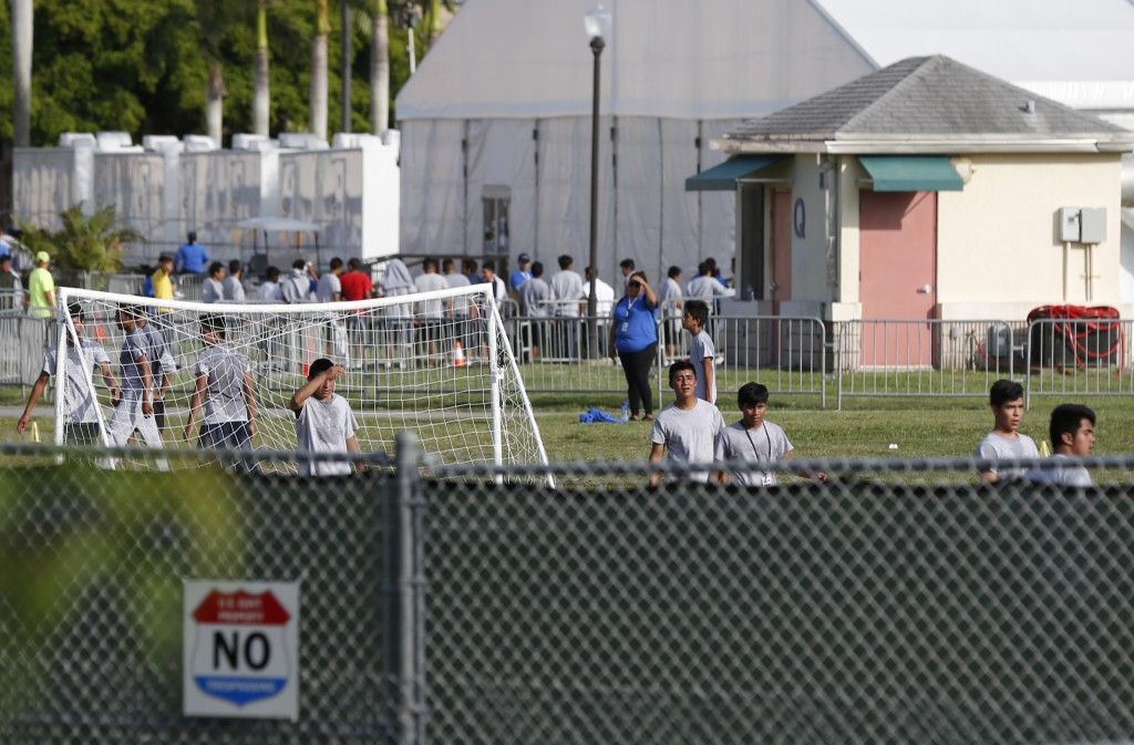 FILE- In this June 18, 2018, file photo immigrant children play outside a former Job Corps site that now houses them in Homestead, Fla. Records obtain...