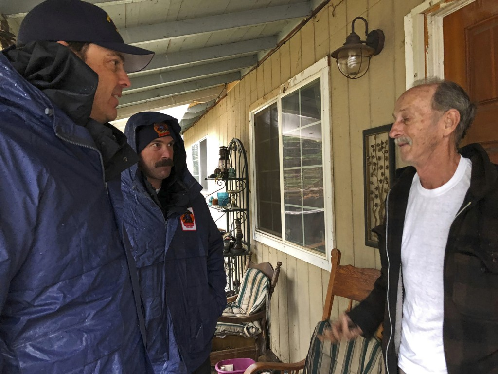 Craig Covey, task force leader for the Orange County search team, left, with David Harper, middle talk to resident Stewart Nugent outside his Paradise...