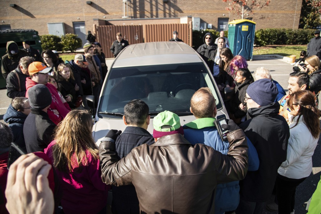 Demonstrators surround a government vehicle after Samuel Oliver-Bruno, 47, an undocumented Mexican national, was arrested after arriving at an appoint...