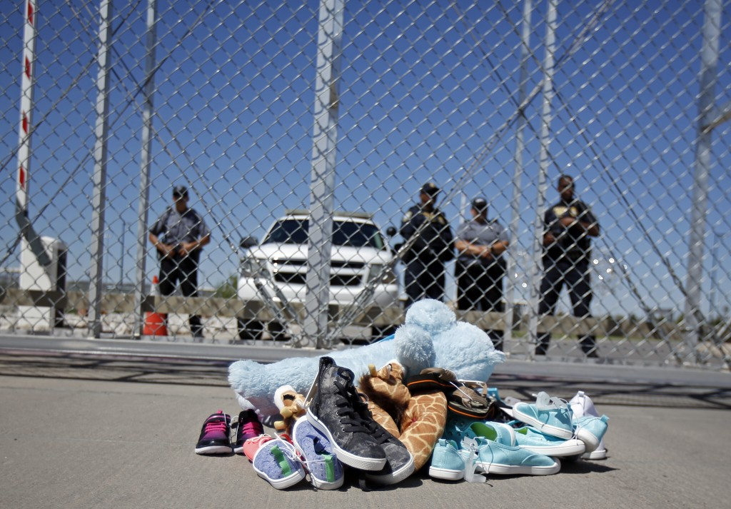 FILE- In this June 21, 2018, photo shoes and a teddy bear, brought by a group of U.S. mayors, are piled up outside a holding facility for immigrant ch