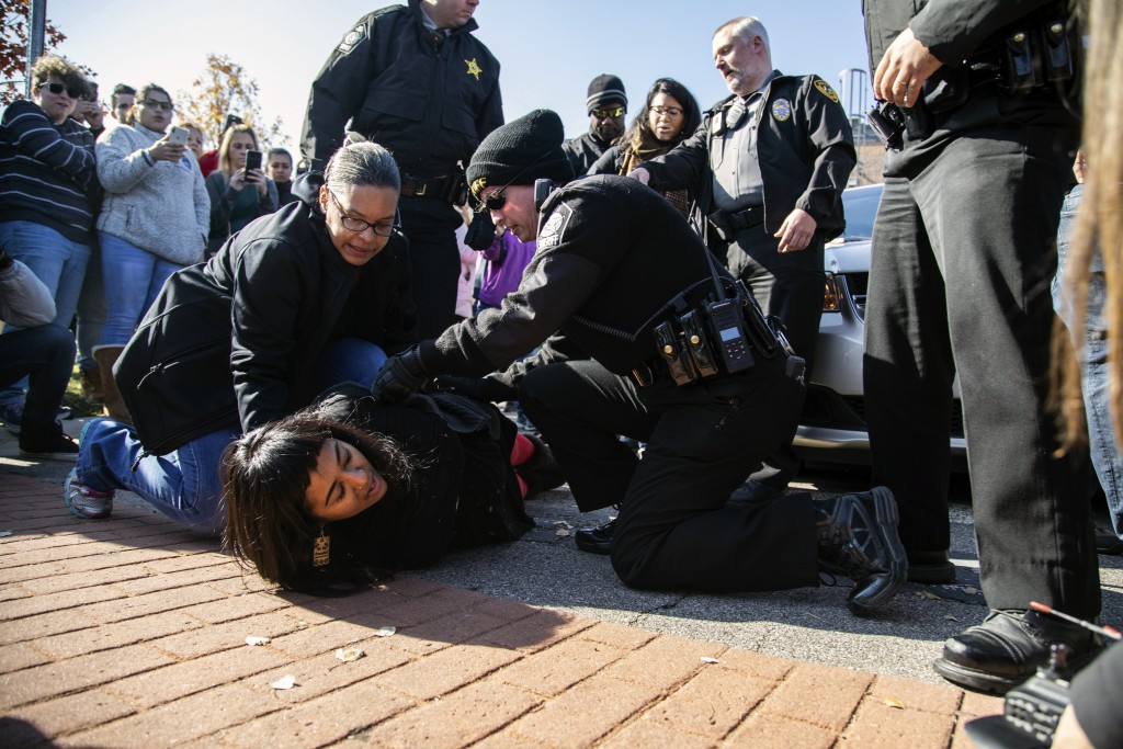 A demonstrator is arrested after Samuel Oliver-Bruno, 47, an undocumented Mexican national, was arrested after arriving at an appointment with immigra...