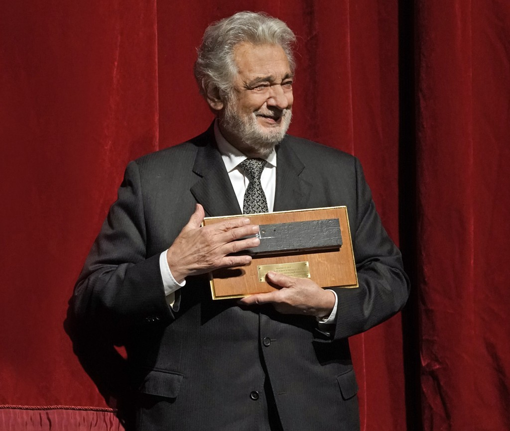 In this photo provided by the Metropolitan Opera, Placido Domingo stands on stage with one of the special gifts he was presented with during a special...