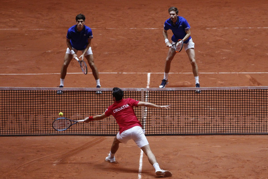 Mate Pavic of Croatia, bottom, returns the ball to France's Nicolas Mahut, right, and Pierre Hughes Herbert during the Davis Cup final between France ...