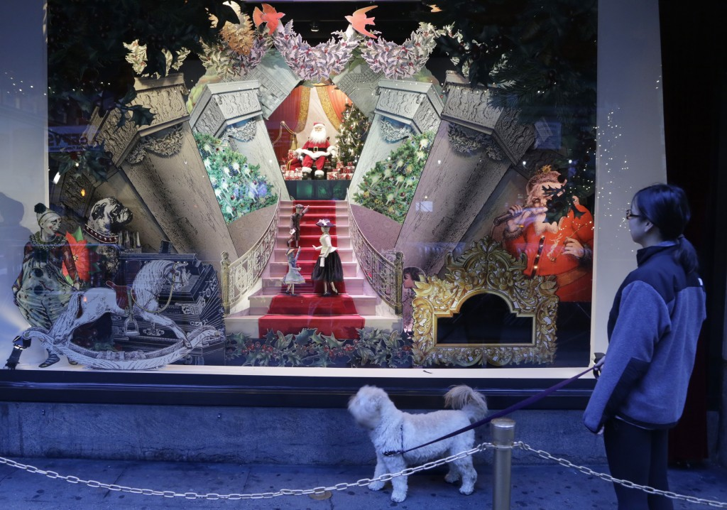 FILE - In this Nov. 18, 2013 file photo, a woman walking her dog passes a vintage Santa Claus holiday window display at Lord & Taylor department store