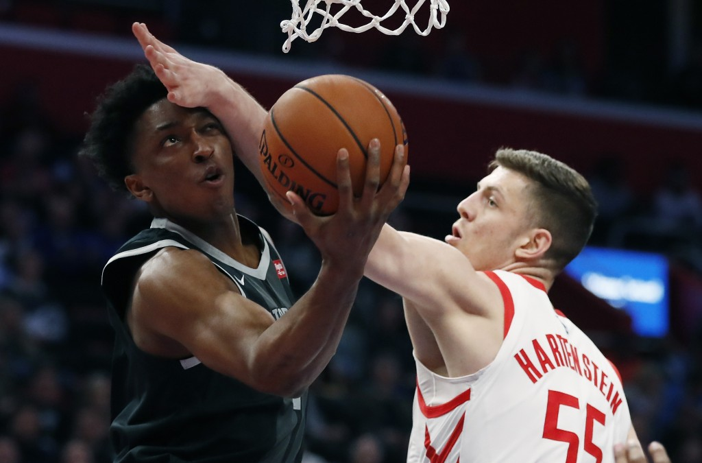 Detroit Pistons forward Stanley Johnson makes a layup as Houston Rockets forward Isaiah Hartenstein (55) defends during the first half of an NBA baske