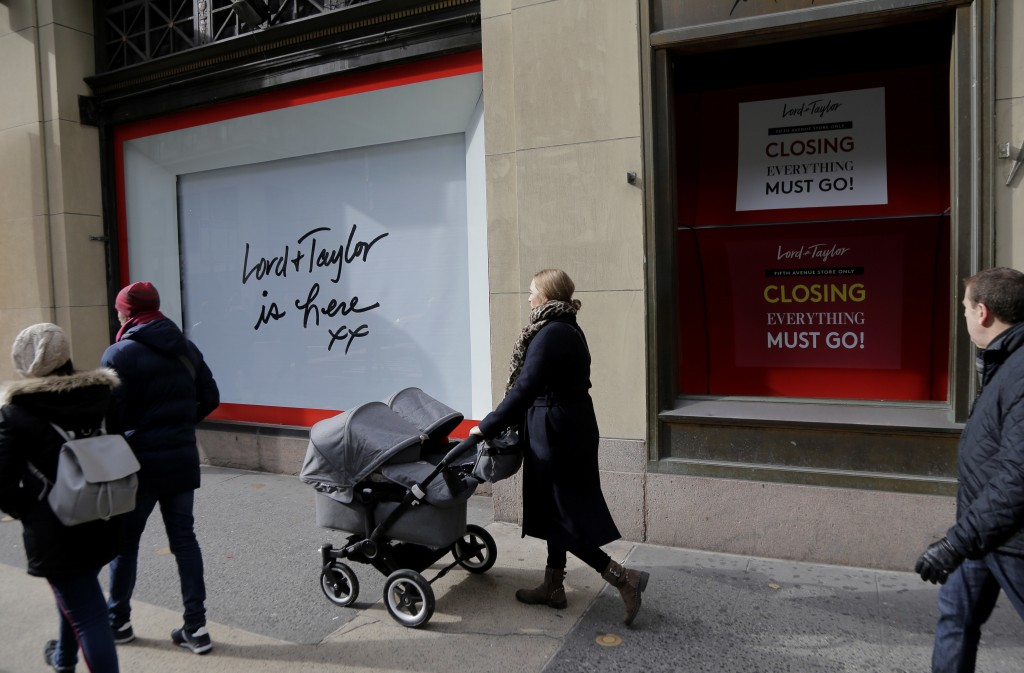 In this Nov. 20, 2018 photo, pedestrians pass by the undercoated windows in the front of Lord & Taylor in New York. Lord & Taylor was the city's first