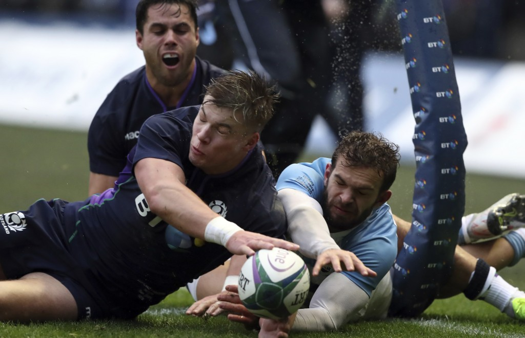 Scotland's Huw Jones, left, Argentina's Matias Orlando, dive for the ball during the rugby union international match between Scotland and Argentina at...