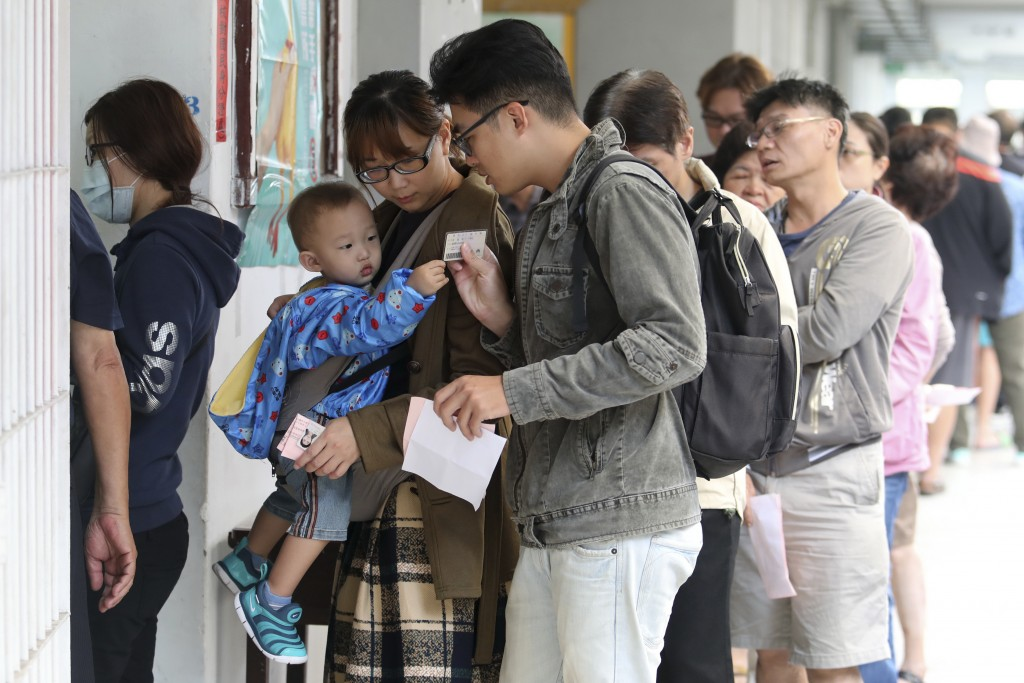 Voters line up at a ballot station to vote for the city mayor in Kaohsiung, Taiwan, Saturday, Nov. 24, 2018. Taiwanese began voting in midterm local e