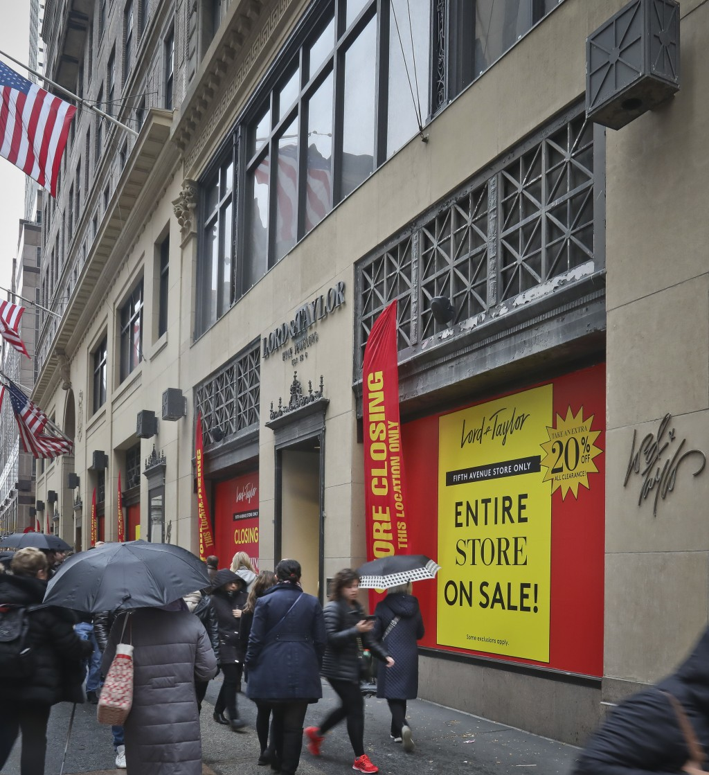 In this Friday, Nov. 9, 2018 photo, closeout sale signs cover windows that annually attracted holiday shoppers and tourists with spectacular Christmas