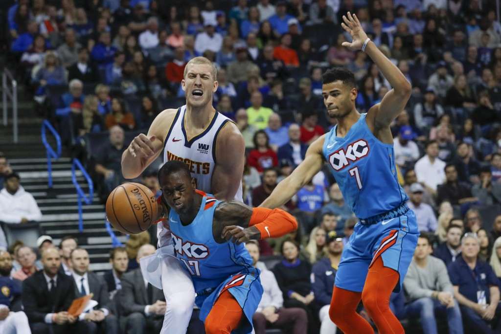 Oklahoma City Thunder guard Dennis Schroder, front, runs into Denver Nuggets forward Mason Plumlee, back, and loses control of the ball as Oklahoma Ci