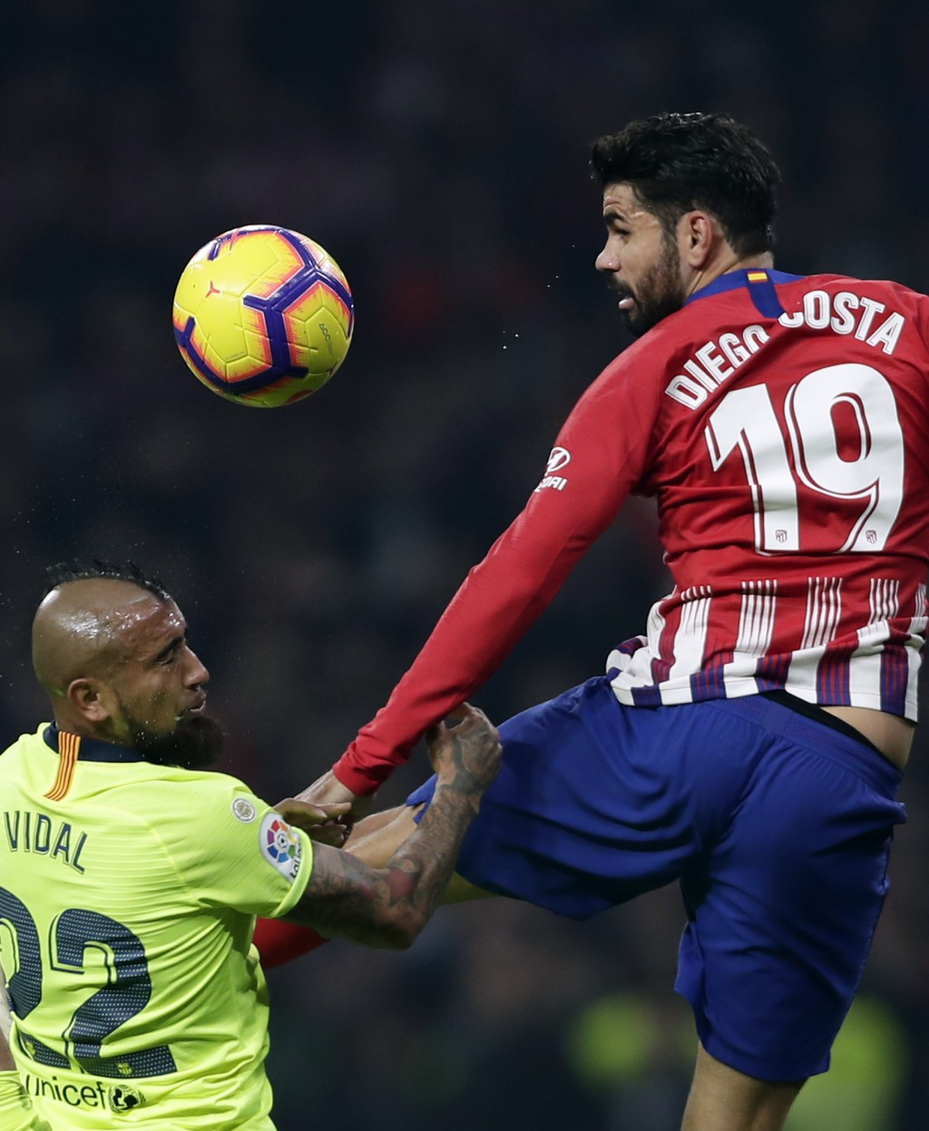 Barcelona's Arturo Vidal, left, duels for the ball with Athletico Madrid's Diego Costa during a Spanish La Liga soccer match between Atletico Madrid a