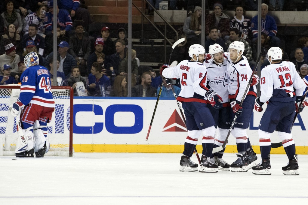 Washington Capitals center Nic Dowd (26) celebrates with teammates after scoring a goal against New York Rangers goaltender Alexandar Georgiev (40) du
