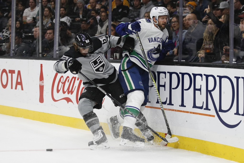 Vancouver Canucks' Alexander Edler, right, of Sweden, is shoved by Los Angeles Kings' Carl Hagelin, also of Sweden, during the second period of an NHL
