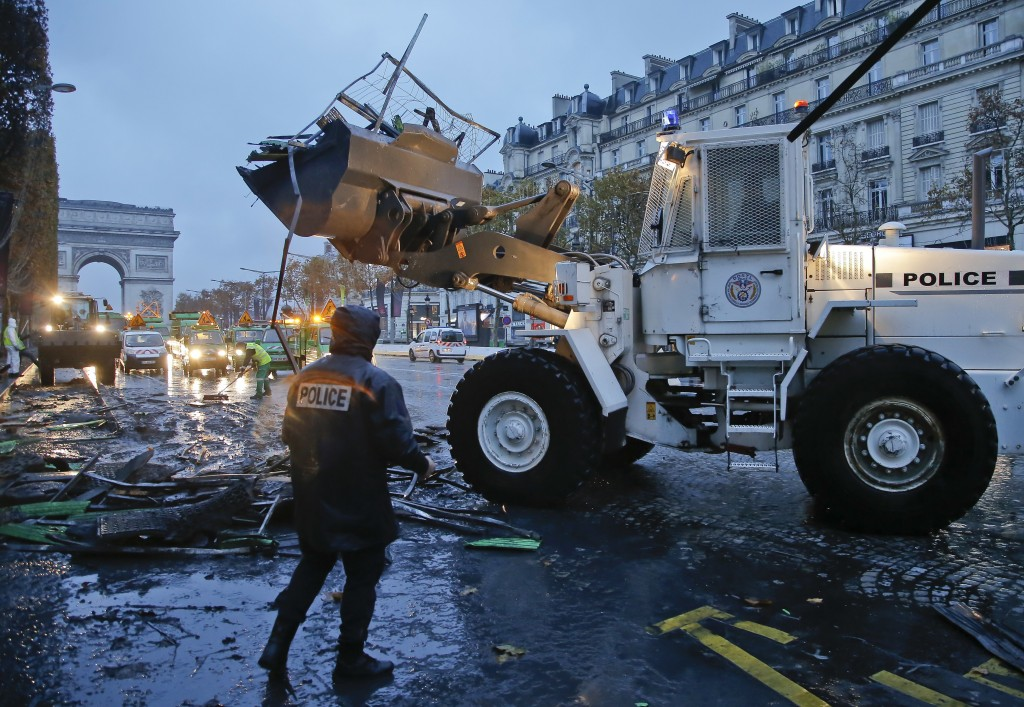 A bulldozer levels the barricade in the aftermath of a protest against the rising of the fuel taxes at the Champs Elysees avenue in Paris, France, Sun