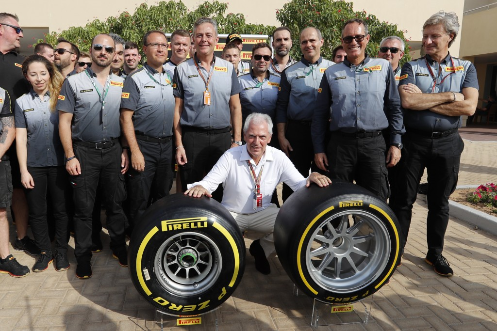 Pirelli CEO Marco Tronchetti Provera, center, poses for a picture with his staff behind the new Pirelli tyre during a presentation ahead of the Emirat...