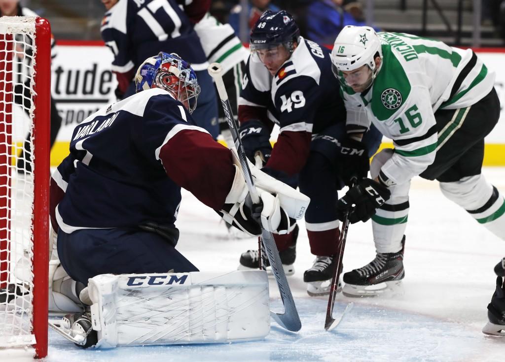 Colorado Avalanche goaltender Semyon Varlamov, left, stops a shot off the stick of Dallas Stars center Jason Dickinson, right, as Colorado defenseman