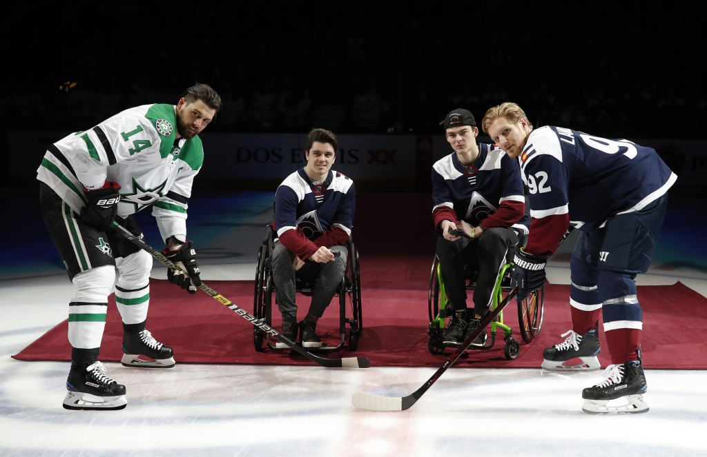 Dallas Stars left wing Jamie Benn, left, and Colorado Avalanche left wing Gabriel Landeskog, right, wait for the ceremonial puck drop by two players f