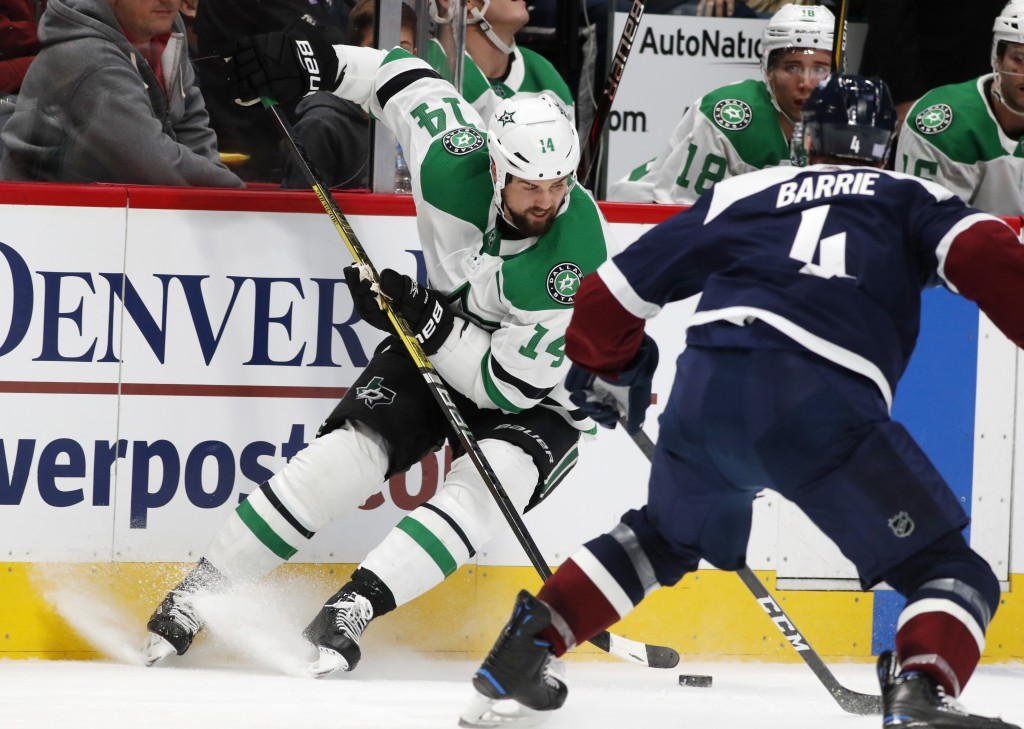 Dallas Stars left wing Jamie Benn, back, looks to pass the puck as Colorado Avalanche defenseman Tyson Barrie covers in the second period of an NHL ho