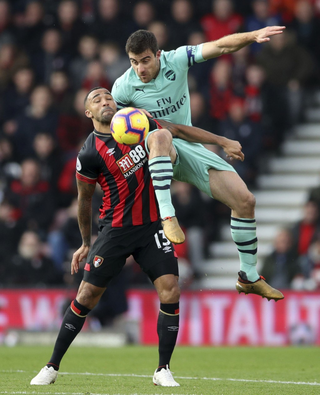 Arsenal's Sokratis Papastathopoulos, top, and Bournemouth's Callum Wilson in action during their English Premier League soccer match at The Vitality S...