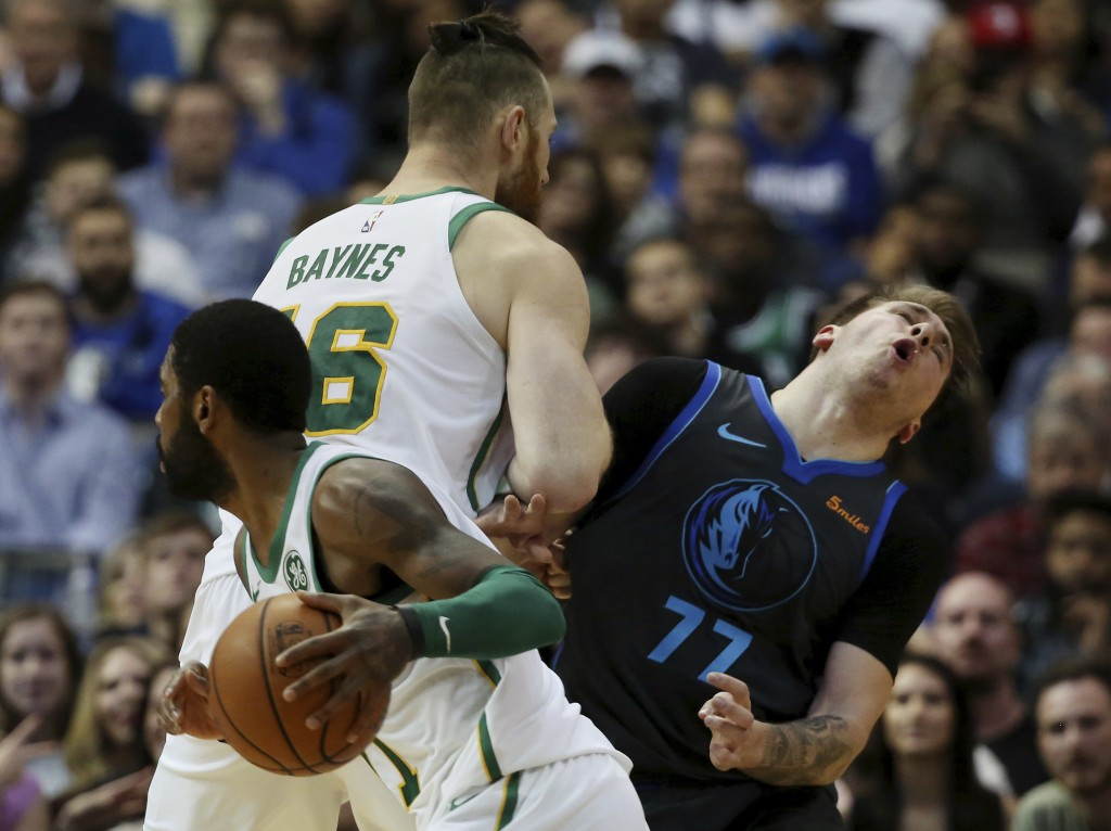 Dallas Mavericks forward Luka Doncic reacts after being blocked on a screen by Boston Celtics center Aron Baynes as teammate guard Kyrie Irving carrie...