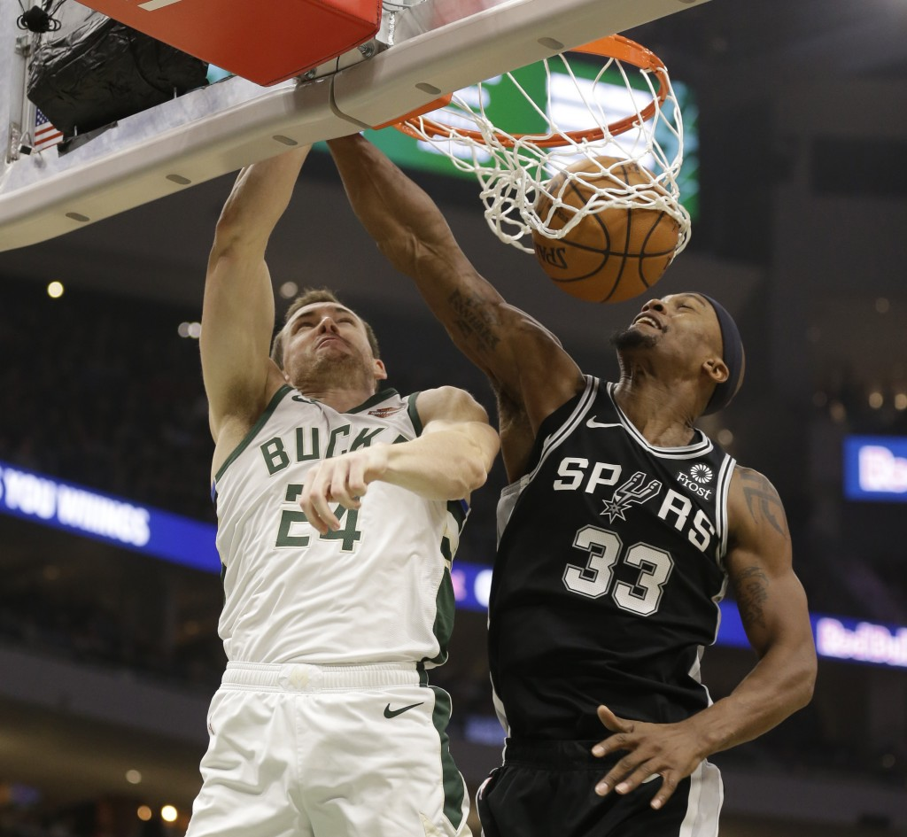 Milwaukee Bucks' Pat Connaughton (24) goes up for a dunk against San Antonio Spurs' Dante Cunningham (33) during the first half of an NBA basketball g