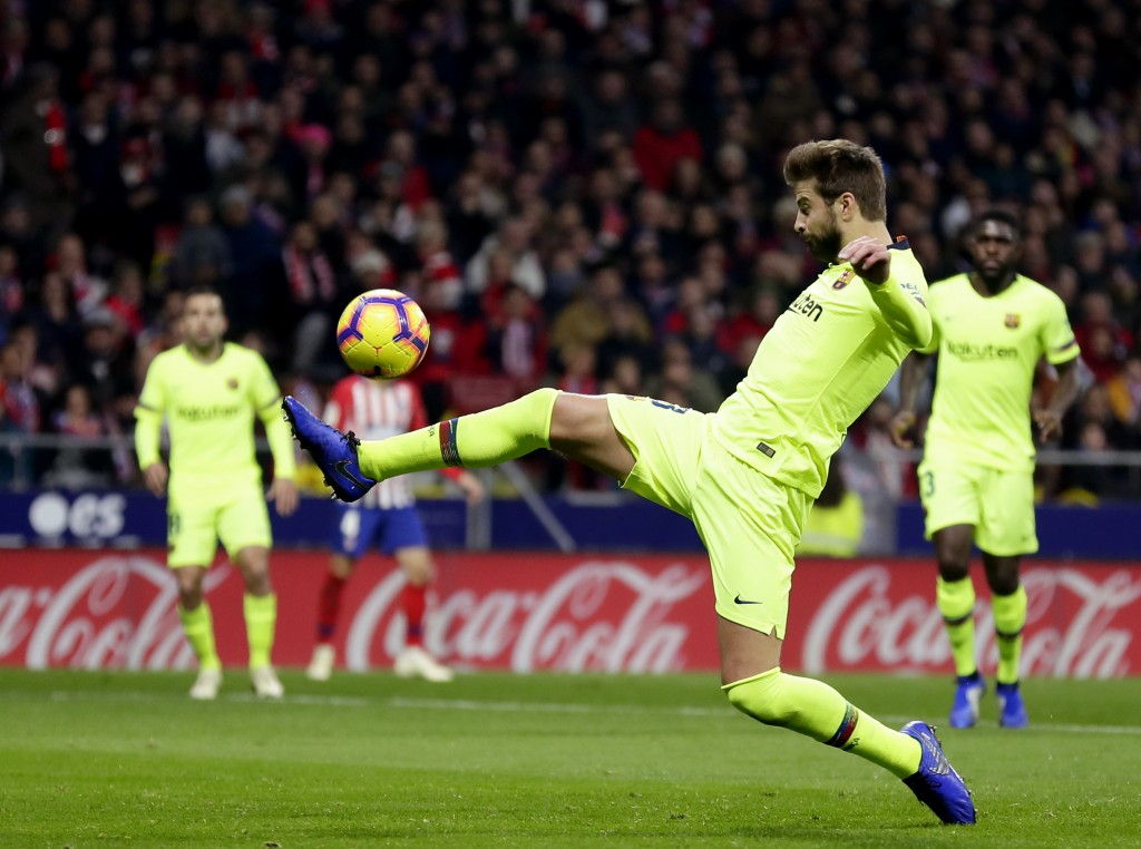Barcelona's Gerard Pique kicks the ball during a Spanish La Liga soccer match between Atletico Madrid and FC Barcelona at the Metropolitano stadium in...