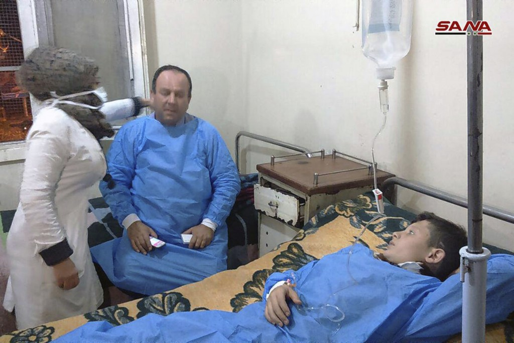 In this photo released by the Syrian official news agency SANA, shows people receiving treatment at a hospital following a suspected chemical attack o...