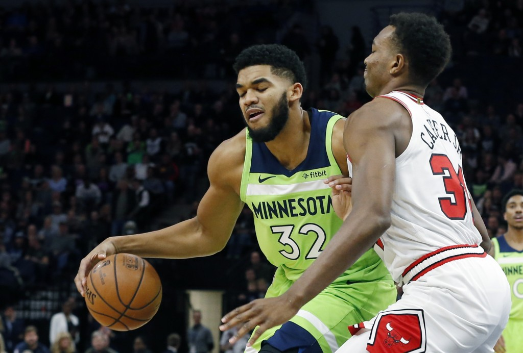 Minnesota Timberwolves' Karl-Anthony Towns, left, works around Chicago Bulls' Wendell Carter Jr. in the first half of an NBA basketball game Saturday,...