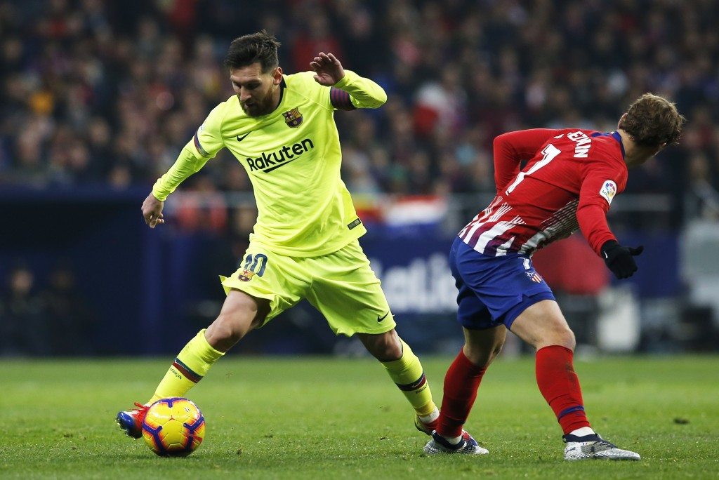 Barcelona's Lionel Messi drives the ball past Atletico's Antoine Griezmann, right, during a Spanish La Liga soccer match between Atletico Madrid and F
