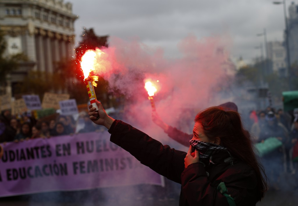 A woman burns a flare during a protest against sexism and gender violence in Madrid, Spain, Sunday, Nov. 25, 2018. Many thousands are expected to join