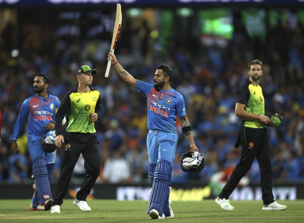 India's Virhat Kohli waves his bat to the crowd as he celebrates his team's six wicket win over Australia in their Twenty20 cricket match in Sydney, S...