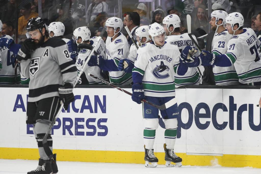 Vancouver Canucks' Adam Gaudette, center, celebrates his goal with teammates as Los Angeles Kings' Drew Doughty skates near them during the second per