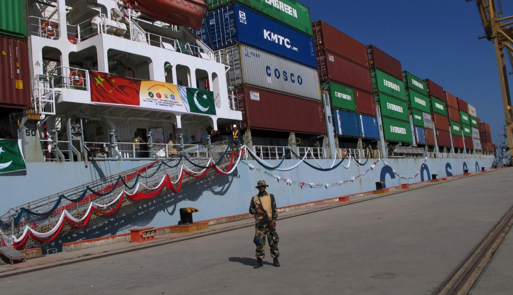 FILE - In this Nov. 13, 2016 file photo, a Pakistan soldier stands guard while a loaded Chinese ship prepares to depart, at Gwadar port, about 700 kil