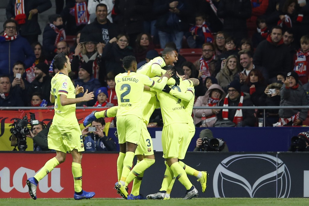 Barcelona players celebrate after Ousmane Dembele scored their first goal during a Spanish La Liga soccer match between Atletico Madrid and FC Barcelo...