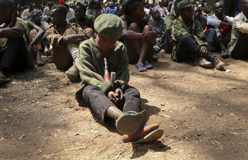 FILE - In this Wednesday, Feb. 7, 2018 file photo, a young child soldier sits on the ground at a release ceremony, where he and others laid down their